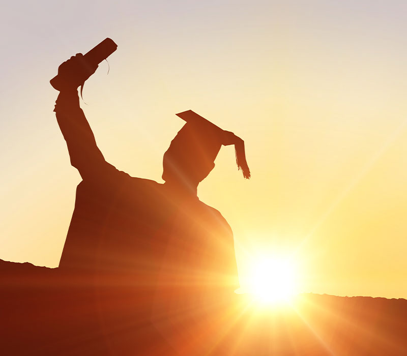 Graduate in silhouette holding up diploma.