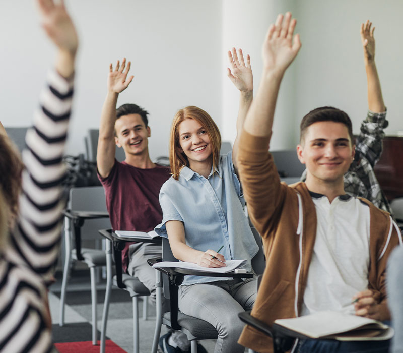 Students raising hands in a classroom.
