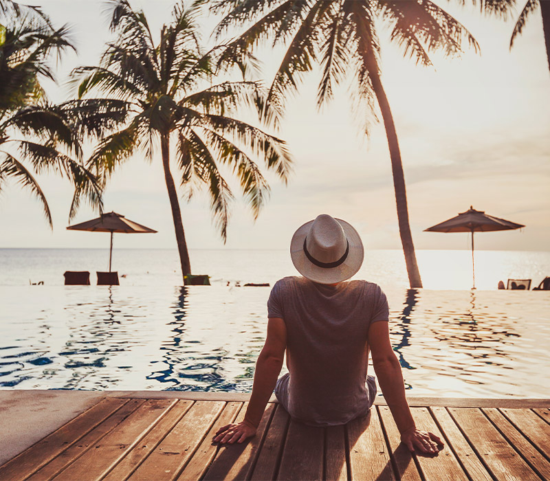 Person vacationing with palm trees and ocean views